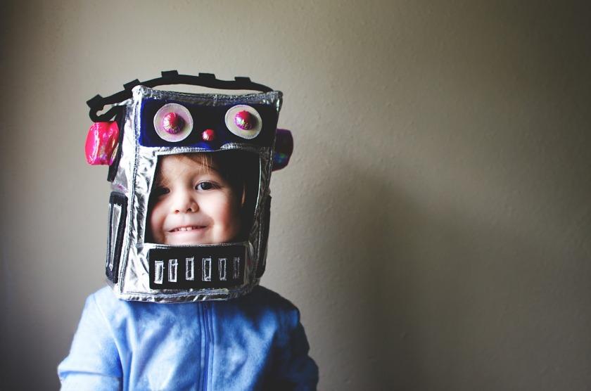 Boy in robot hat/mask, kid smiling in robot costume.